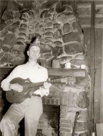 Ralph Lutz playing a lute in front of the stone fireplace.